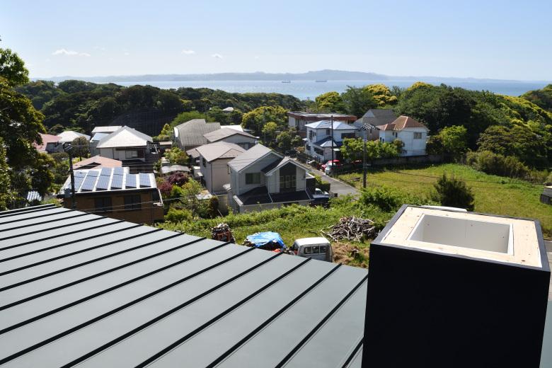 海の良く見える屋根の上での煙突工事